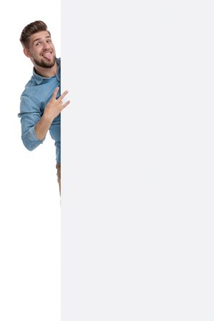 Casual man making a funny face and sign behind a blank billboard while standing on white studio background Reklamní fotografie