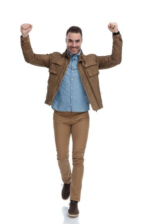 Cheerful casual man celebrating with his hand in the air while wearing a leather jacket and walking on white studio background Reklamní fotografie