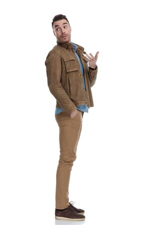 Side view of casual man explaining with his hand in his pocket while wearing a leather jacket and standing on white studio background