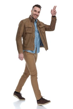 Positive casual man smiling and welcoming while wearing a leather jacket and stepping on white studio background