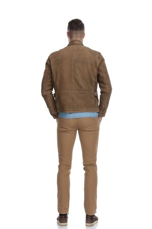 Rear view of confident casual man holding both hands in his pockets while wearing a leather jacket and standing on white studio background