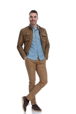 Positive casual man smiling with both hands in his pockets while wearing a leather jacket and stepping on white studio background Reklamní fotografie