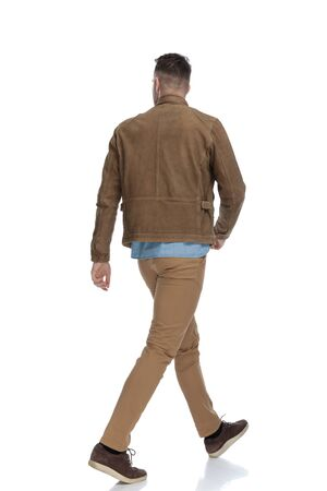 Rear view of a eager casual man wearing a leather jacket while walking on white studio background Reklamní fotografie