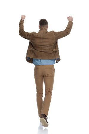 Rear view of casual man celebrating with his hand in the air while wearing a leather jacket and walking on white studio background Reklamní fotografie