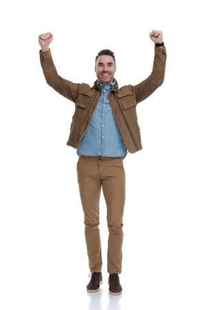 Happy casual man celebrating and smiling while wearing a leather jacket and standing on white studio background