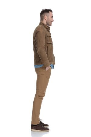 Side view of handsome casual man holding both hands in his pockets while wearing a leather jacket and standing on white studio background