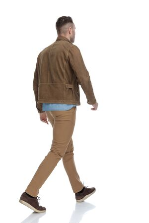 Rear view of a determined casual man wearing a leather jacket while walking on white studio background