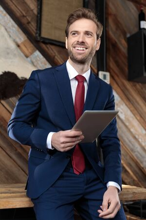 happy young model wearing suit smiling and holding a tab, looking to side and sitting in a coffeeshop Banque d'images