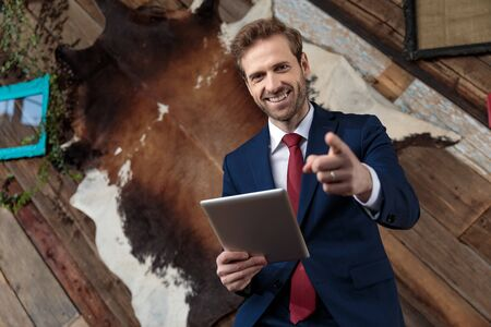 happy young businessman holding tab and pointing finger, smiling and sitting in a coffeeshop