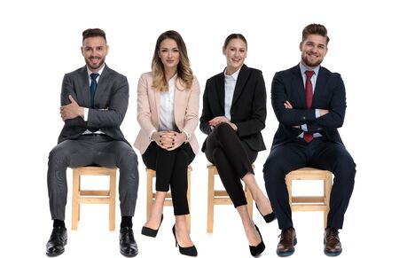 Team of 4 positive businessmen smiling and holding their arms crossed while sitting on chairs on white studio background