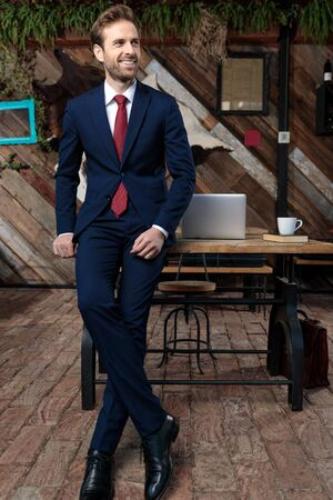 happy young businessman smiling and looking to side, sitting in a coffeeshop, full body