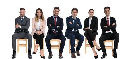 Team of 6 trustworthy businessmen smiling and looking forward while sitting on chairs on white studio background Stock Photo