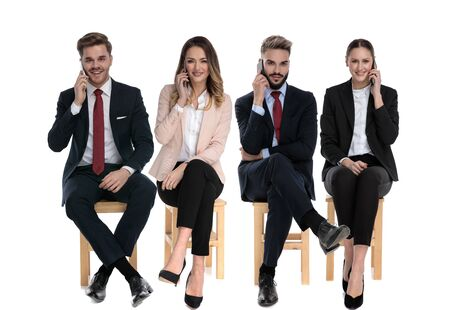 Team of 4 businessmen talking on their phones while waiting for a job interview sitting on chairs on white studio background Stock Photo