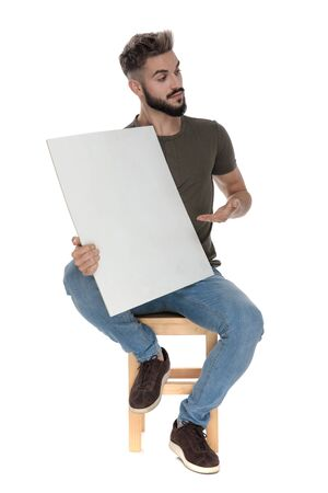 Friendly casual man presenting a blank billboard, sitting on a chair on white studio background