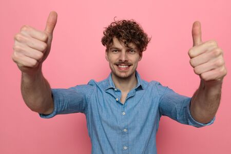 enthusiastic casual young model making thumbs up sign and smiling, standing on pink background