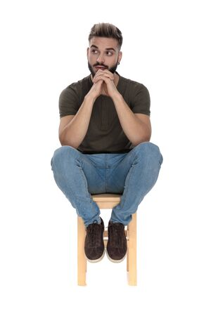 Wondering casual man looking away and holding his hands together while sitting on a chair on white studio background Banco de Imagens