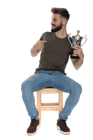 Happy casual man holding a trophy and pointing at it while sitting on a chair on white studio background Standard-Bild