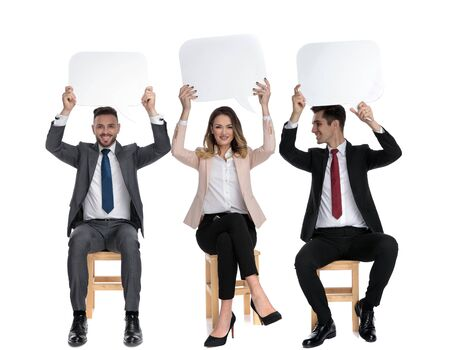 Three positive businessmen holding speech bubble above their heads while sitting on chairs on white studio background Stock Photo