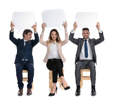 Three businessmen holding speech bubble above their heads while sitting on chairs on white studio background