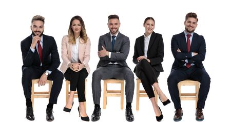 Team of 5 happy businessmen smiling while waiting for a job interview sitting on chairs on white studio background Stock Photo
