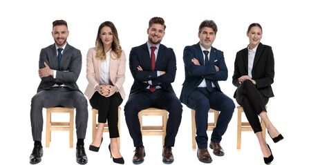 Team of 5 positive businessmen smiling while waiting for a job interview sitting on chairs on white studio background