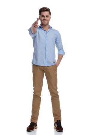 Positive casual man holding finger gun and hand in pocket while wearing shirt and standing on white studio background