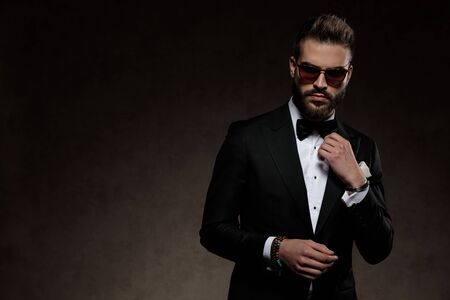 Handsome fashion groom adjusting his collar while wearing sunglasses and suit, standing on a wallpaper studio background Stockfoto