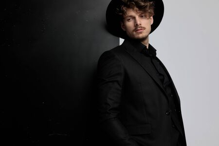 Thoughtful fashion model looking away and thinking while wearing suit and hat, standing on black and white studio background