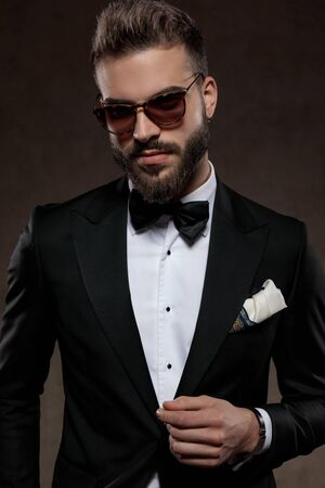 Positive fashion groom smiling while wearing suit and sunglasses, standing on a wallpaper studio background Stockfoto