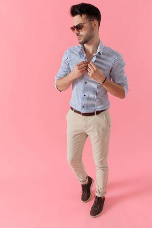 Pensive smart casual man unbuttoning his shirt wearing sunglasses, walking on pink studio background