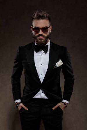 Handsome fashion groom looking forward with both hands in pockets while wearing suit and sunglasses, standing on a wallpaper studio background