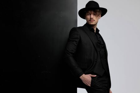 Eager fashion model looking away with his hand in his pocket while wearing suit and hat, standing on black and white studio background