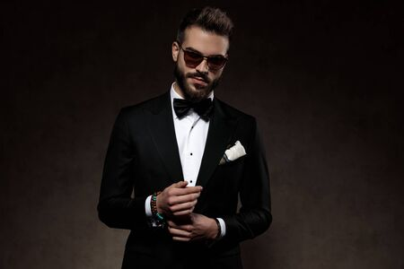 Positive fashion groom adjusting his sleeve and smiling while wearing sunglasses and suit, standing on a wallpaper studio background Stockfoto