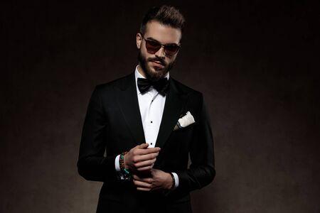 Positiver Modebräutigam, der seinen Ärmel anpasst und lächelt, während er Sonnenbrille und Anzug trägt und auf einem Tapetenstudiohintergrund steht Standard-Bild