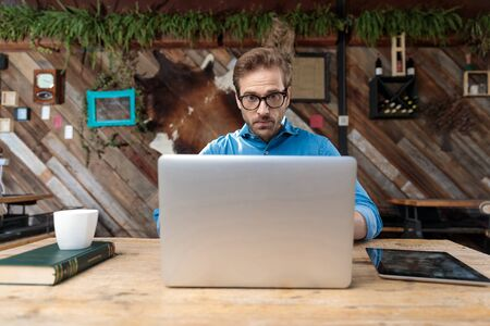 casual man wearing glasses sitting at desk and looking at laptop surprised at the coffeeshop