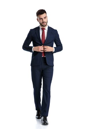 attractive businessman wearing navy suit walking while closing his jacket and looking away with style on white studio background