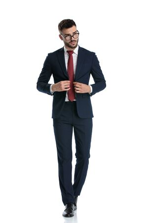 handsome formal man wearing glasses walking while closing his jacket and posing with cool attitude on white studio background Banque d'images