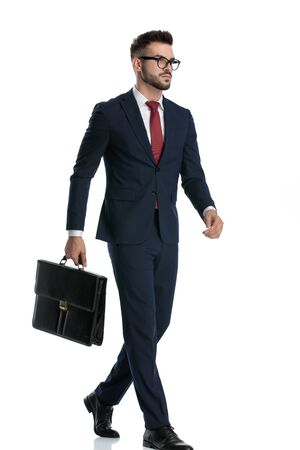 side view of a businessman wearing glasses walking with briefcase on hand and looking ahead serious on white studio background Banque d'images