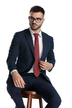 businessman wearing glasses sitting while fixing jacket and striking a pose with serious attitude on white studio background