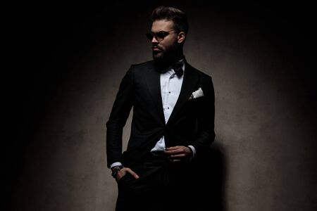 businessman wearing sunglasses standing with hand in pocket and striking a pose with cool attitude on dark studio background Archivio Fotografico