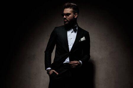 homme d'affaires portant des lunettes de soleil debout avec la main dans la poche et prenant une pose avec une attitude cool sur fond de studio sombre Banque d'images