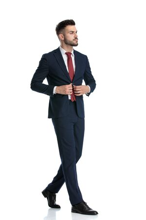 side view of a handsome businessman wearing navy suit walking while fixing his jacket with style on white studio background