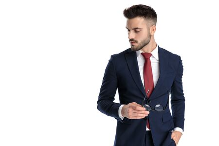 attractive businessman wearing navy suit standing with one hand in pocket holding glasses with the other and looking down with attitude on white studio background