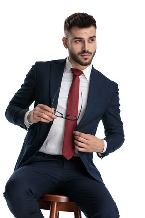 businessman wearing navy suit sitting while taking off his glasses with cool attitude and fixing jacket on white studio background Foto de archivo