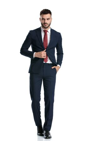 sexy formal guy wearing navy suit walking with hand in pocket and fixing his jacket with serious attitude on white studio background