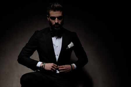 attractive businessman wearing black tuxedo sitting and holding hands on his jacket's button serious on dark studio background Banco de Imagens