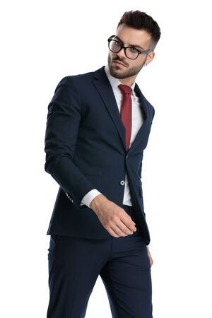 sexy formal man wearing glasses walking and looking back over shoulder with cool attitude on white studio background