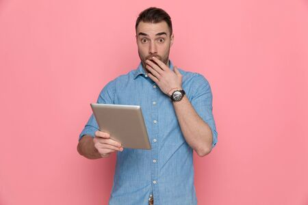 young casual man holding his tablet and covering his mouth on pink studio background