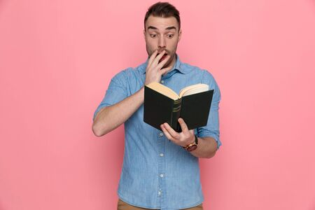 young shocked casual man reading his book and touching his face on pink studio background