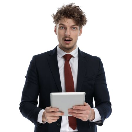 Amazed businessman holding tablet and gasping while wearing suit and standing on white studio background Imagens
